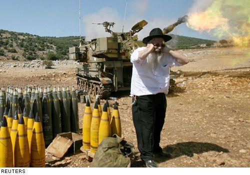 Judíos ultra ortodoxos cubren sus oídos del ruido producido por la artillería israelí que realiza ataques contra localidades en la frontera libanesa, para atacar objetivos del grupo Hezbolá.