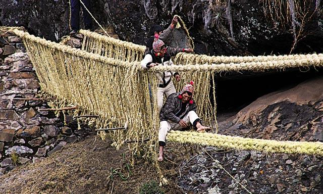 VÍA ANCEsTRAL. Campesinos K'anas trenzan los gruesas sogas de Ichu para renovar la estructura antigua del puente. Lo hacen cada año en junio.